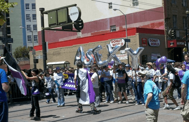 A group of people waving or wearing the asexual flag, holding up metallic inflatable letters spelling 'ASEXY' and holding purple balloons during a pride march.